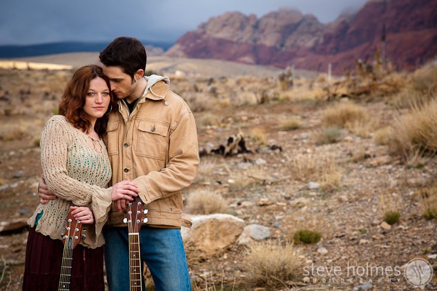 Husband and wife embracing with guitars at Red Rocks.