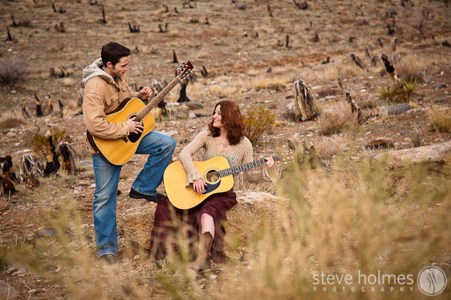 Couple playing guitars in the desert.