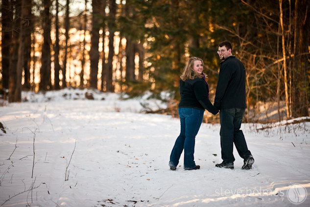 Couple walking along a trail in the woods during their winter engagement session.