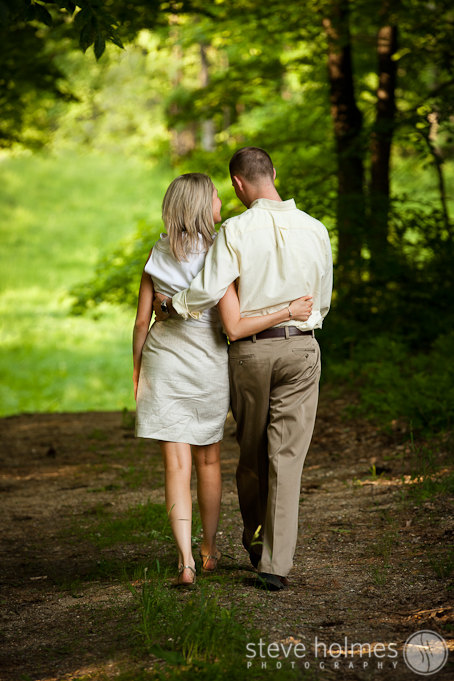 Couple walking on a trail in the woods during their engagement session at Stonewall Farm