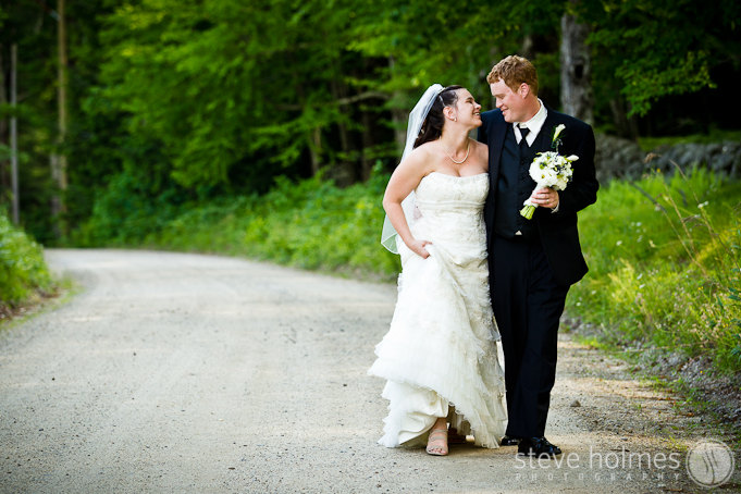 Bride and groom walking down a country road together.