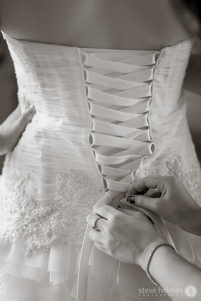 A stunning black and white close up of the back of the brides dress.