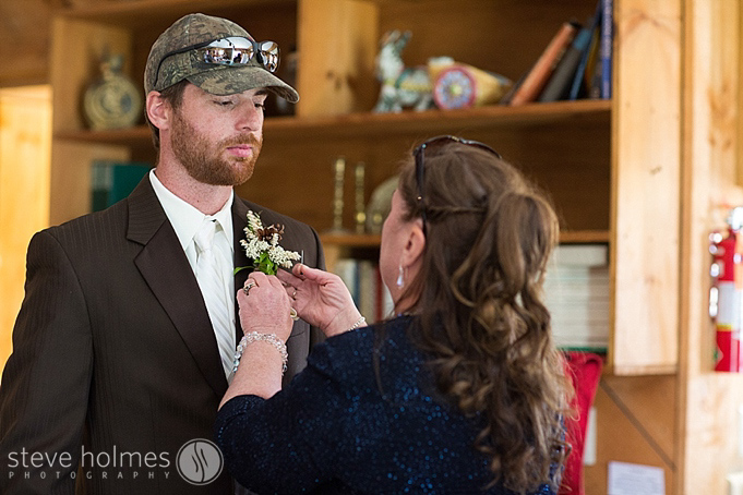 The groom getting his boutonierer pinned.