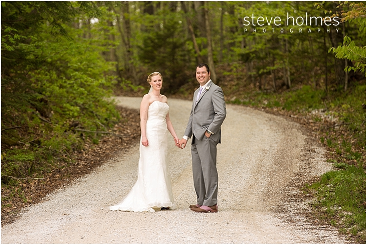 23_bride-and-groom-standing-on-road-leading-into-the-woods