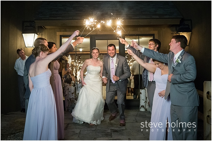 66_wedding-guests-hold-sparklers-for-bride-and-groom-to-walk-under