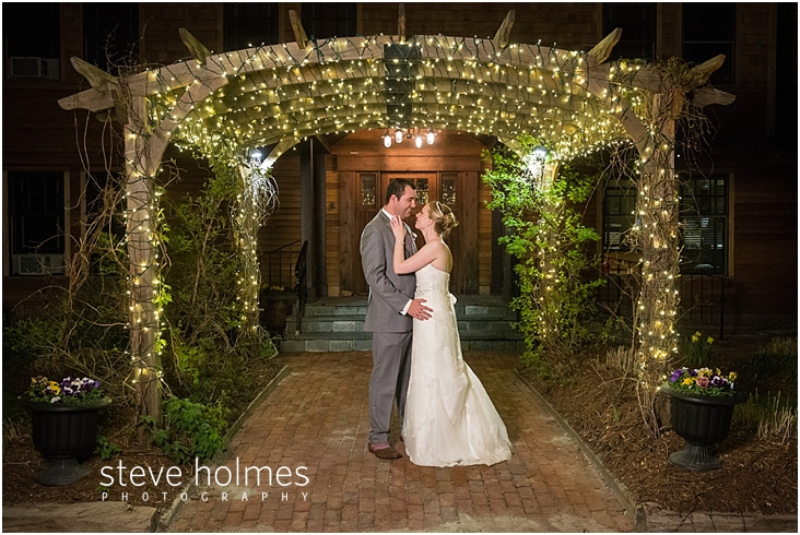 68_bride-and-groom-smile-under-pergola-wrapped-in-white-lights