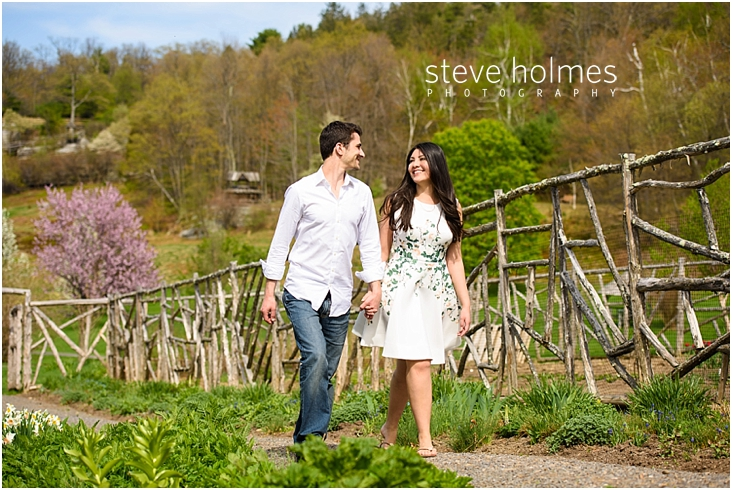 19_happy-couple-smile-holding-hands-walking-by-wooden-fence