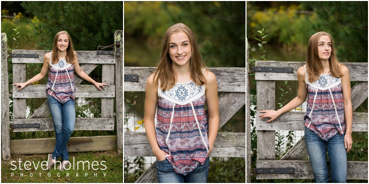 05_Keene-High-School-Senior-Pictures-Outdoors-Wooden-Gate-Blue-and-Red-Patterned-Tank-Top-Jeans