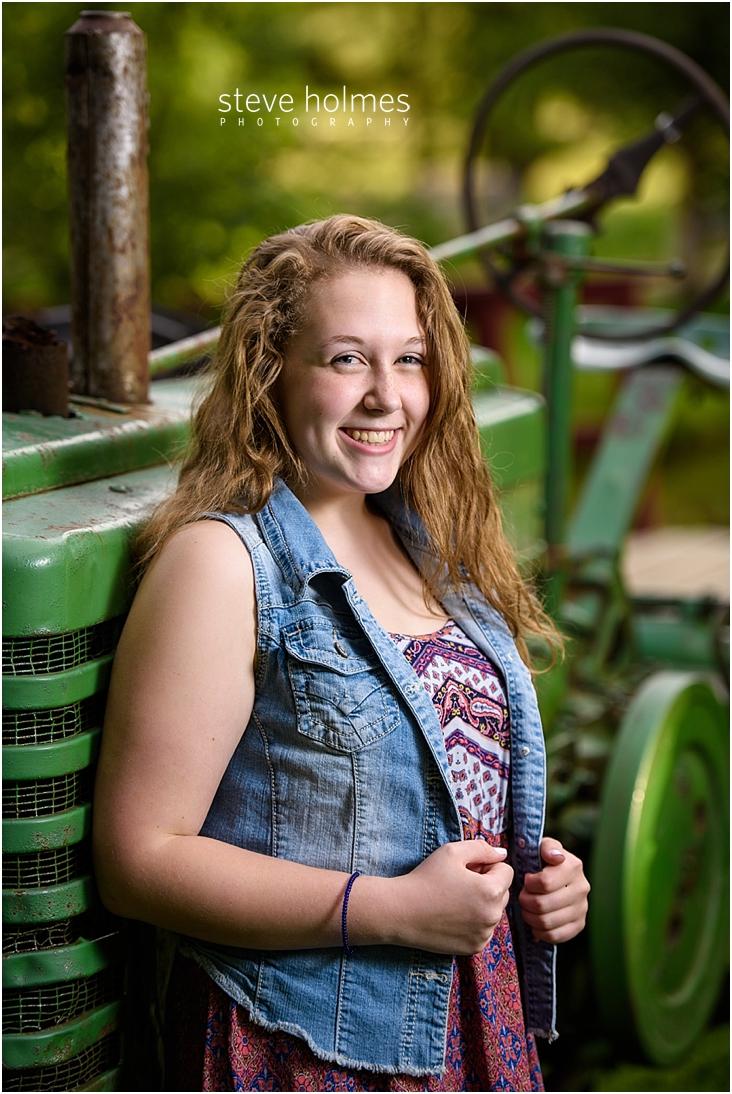 06_Keene-High-School-Senior-Pictures-Outdoors-Green-Tractor-Denim-Vest-Patterned-Dress