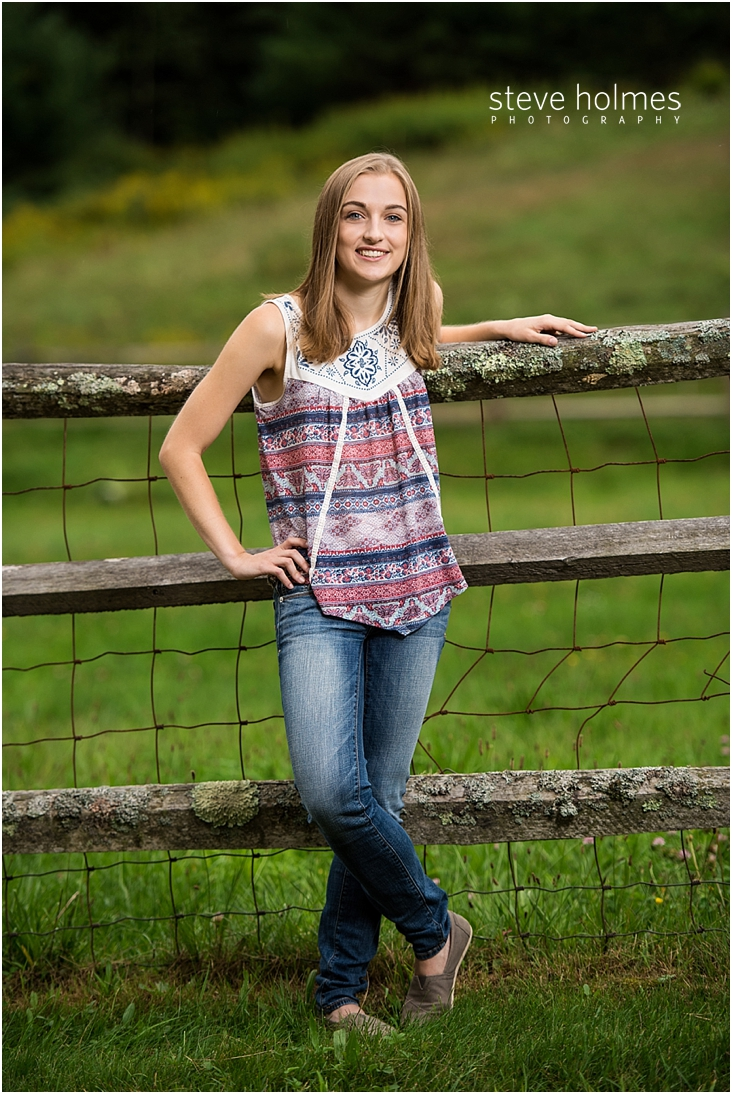 10_Keene-High-School-Senior-Pictures-Outdoors-Wooden-Fence-Blue-and-Red-Patterned-Tank-Top-Jeans