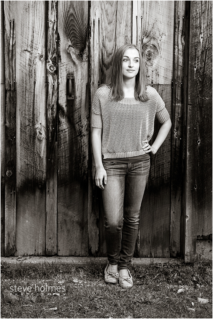 18_Keene-High-School-Senior-Pictures-Outdoors-Wood-Wall-Tan-Sweater-Jeans-Black-and-White