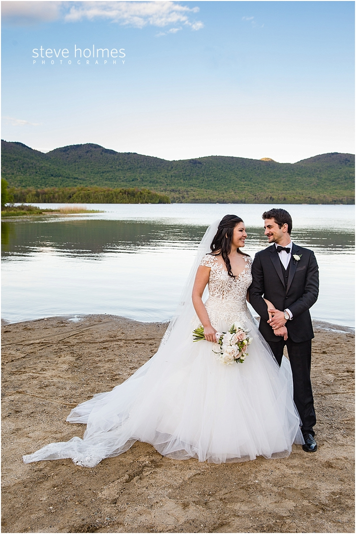 104_bride-and-groom-standing-on-the-beach-with-lake-and-mountains-behind-them