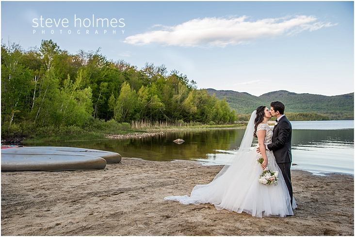 108_bride-and-groom-kiss-on-beach-looking-at-each-other-with-lake-canoes-and-mountains-in-background
