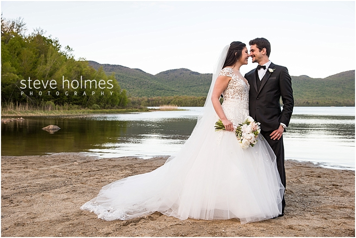 111_bride-and-groom-stand-on-beach-looking-at-each-other-with-lake-canoes-and-mountains-in-background