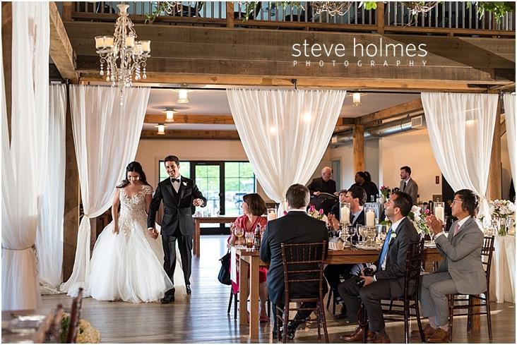 116_bride-and-groom-enter-reception-as-guests-clap