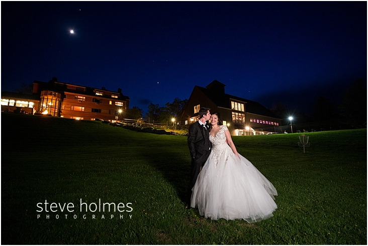 126_groom-kisses-brides-head-outside-at-night-with-reception-in-background