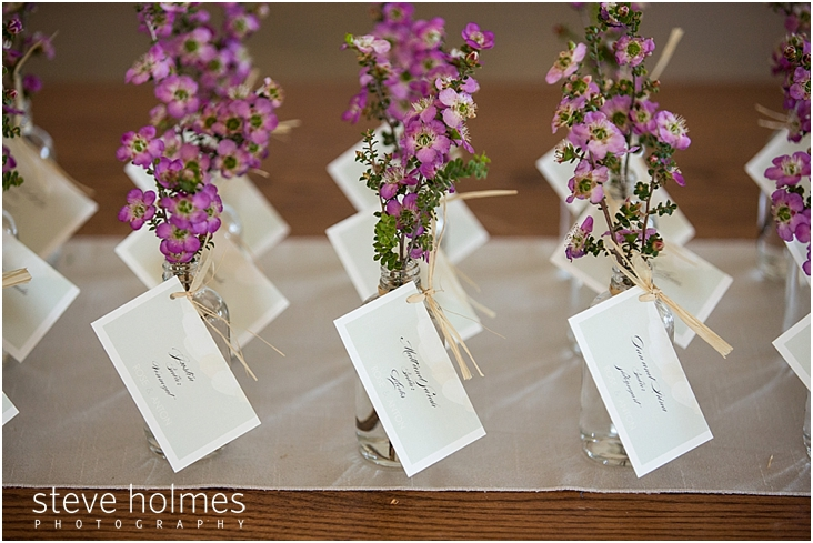 29_guest-name-cards-attached-to-clear-glass-vases-with-pink-wildflowers
