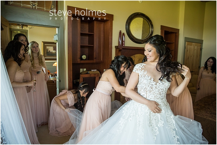 45_bride-smiles-as-bridesmaids-help-with-her-dress