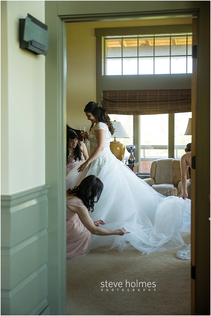 47_view-from-doorway-of-_bride-smiling-as-bridesmaids-help-with-her-dress