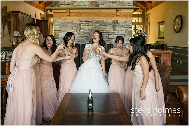 49_bride-and-bridesmaids-laugh-as-they-toast-champagne