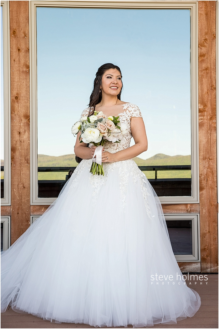 50_bride-stands-in-front-of-window-with-bouquet