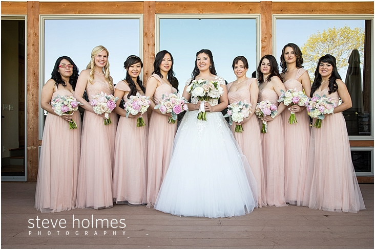51_bride-and-bridesmaids-stand-on-balcony-in-front-of-large-windows