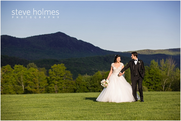 97_bride-and-groom-hold-hands-with-mountains-in-background