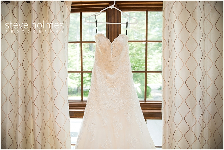 02_beaded-strapless-wedding-dress-hanging-in-front-of-window