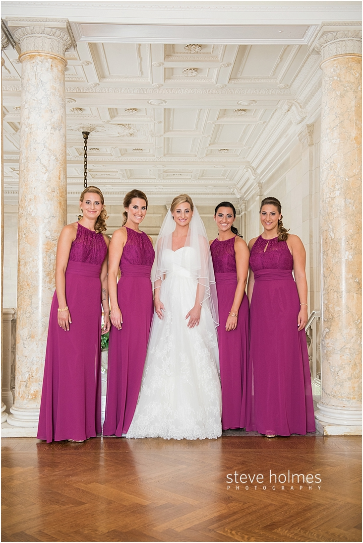 22_bride-and-bridesmaids-stand-at-top-of-staircase