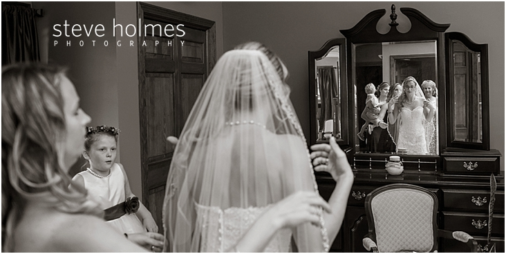 22_bride-looks-in-mirror-as-bridesmaid-helps-with-veil-black-and-white