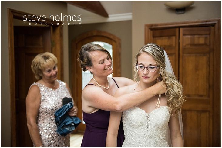 24_bridesmaid-helps-put-necklace-on-bride