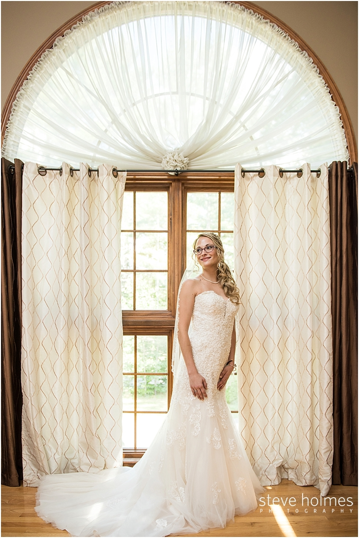 26_brides-smiles-as-she-stands-in-front-of-window