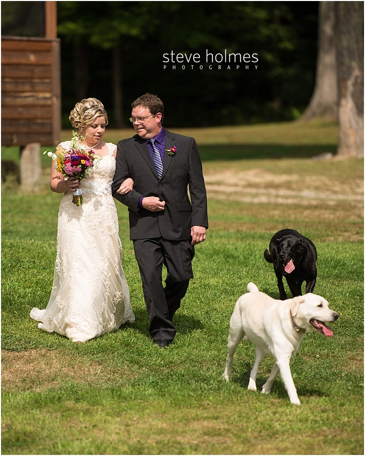 35_bride-walks-to-ceremony-with-father-and-two-dogs