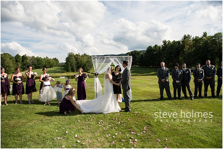 39_bride-and-groom-holding-hands-during-outdoor-ceremony-as-bridesmaid-fixes-train