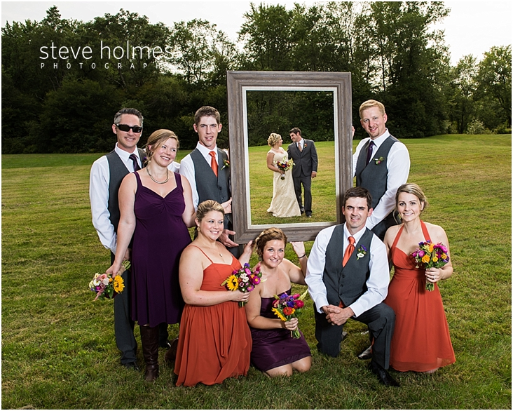 44_wedding-party-holding-large-picture-frame-with-bride-and-groom-standing-behind