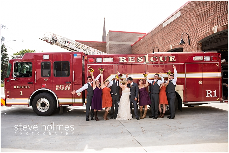 46_bride-and-groom-kiss-wedding-party-cheers-in-front-of-red-fire-truck
