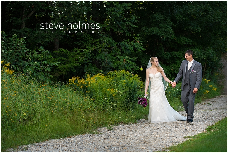 54_bride-and-groom-walk-holding-hands-down-gravel-path