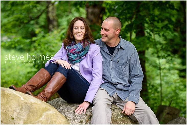 03_happy-couple-laughin-while-sitting-on-large-rock