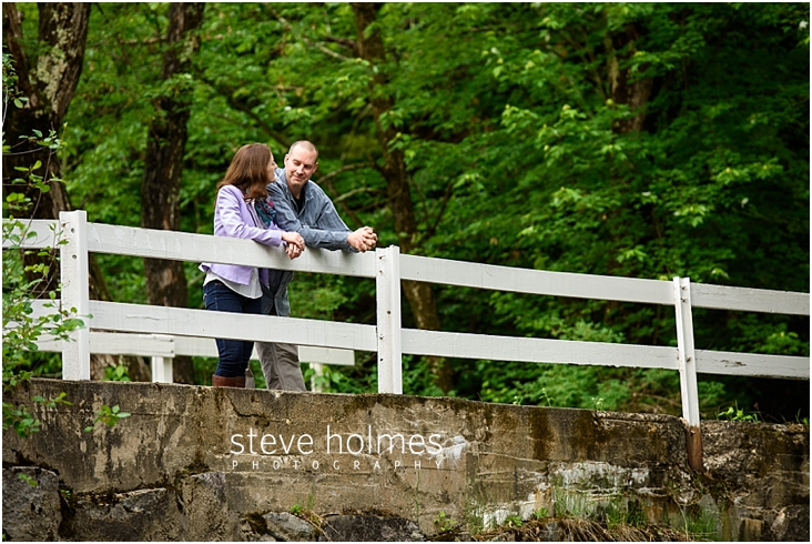 06_happy-couple-looking-at-each-other-while-leaning-on-white-wooden-fence