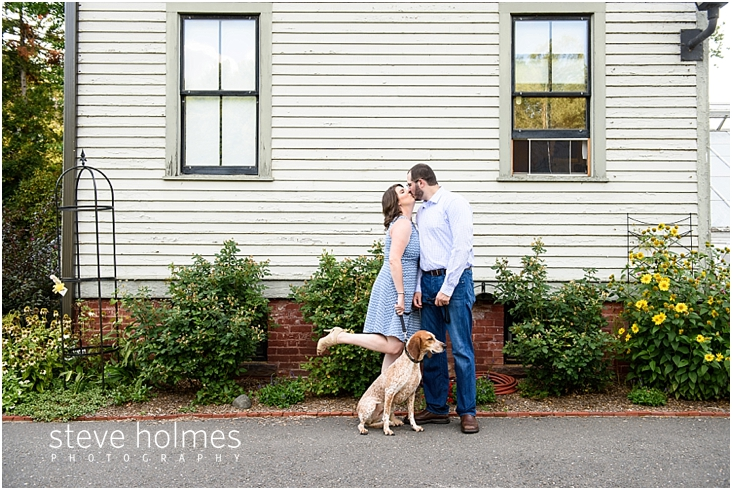 04_couple-kissing-outside-of-home-while-holding-leash-of-their-dog