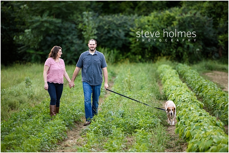 14_happy-couple-holding-hands-while-walking-through-farm-field-with-dog