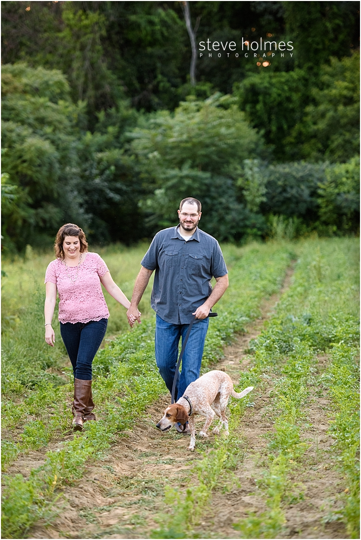 15_happy-couple-holding-hands-while-walking-through-farm-field-with-dog