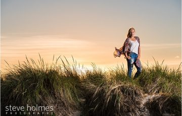 015_teen-standing-on-rock-with-grass-and-sunset-in-background