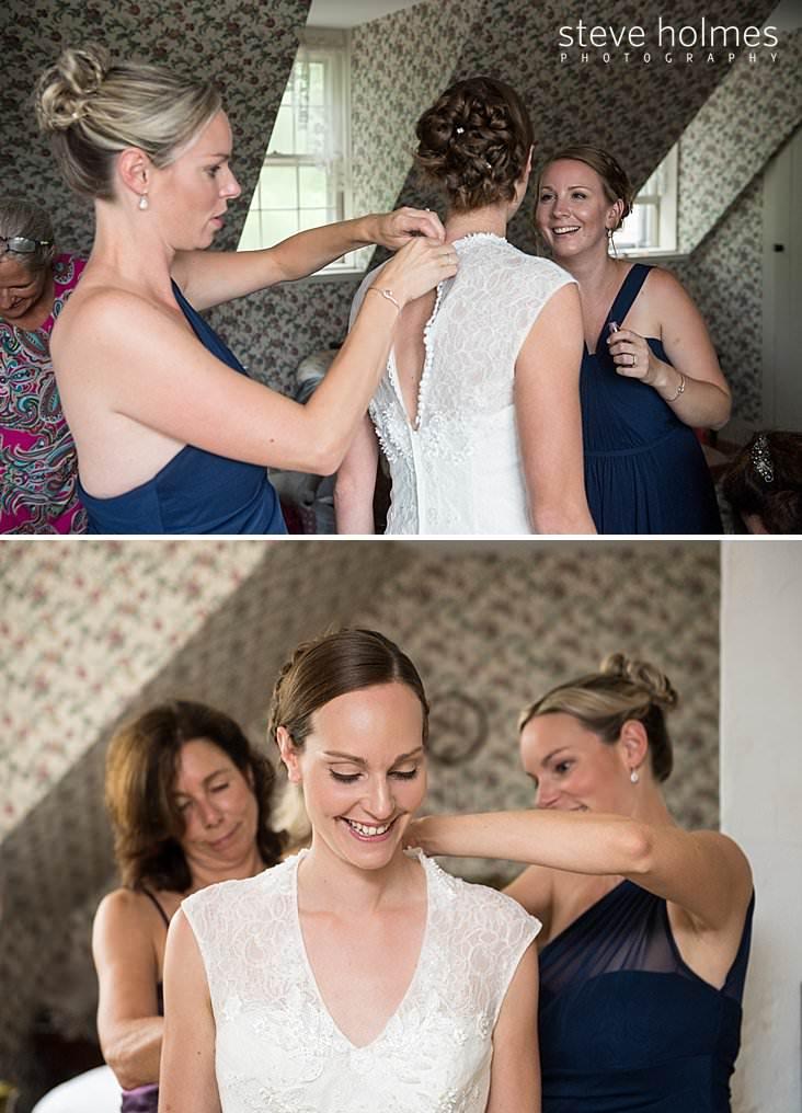 28_Bridesmaid buttons bride into her wedding dress.jpg