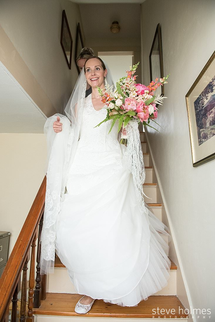 31_Bride in veil with bouquet comes down the stairs.jpg