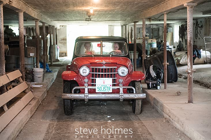 34_Bride and father drive through barn in antique car.jpg