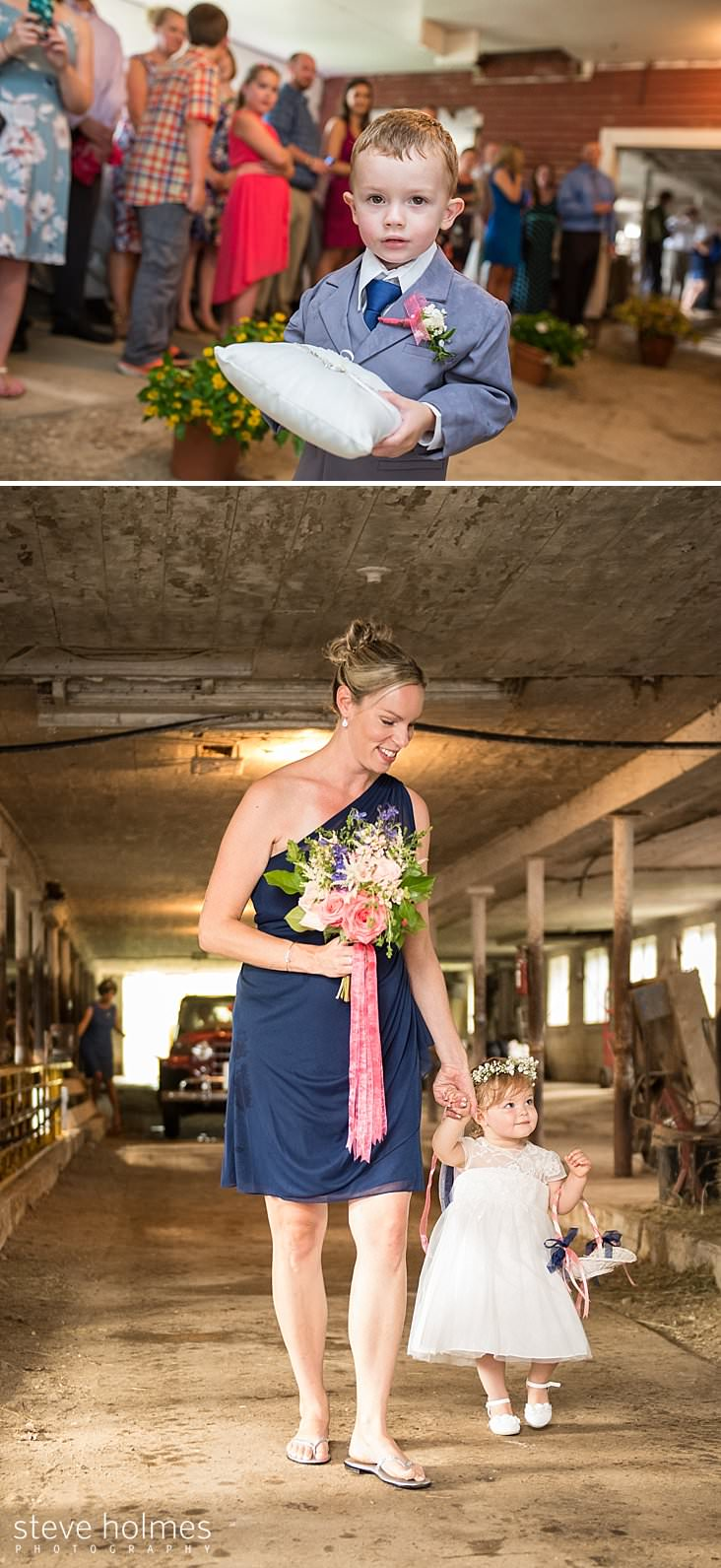 35_Ring bearer stands in barn with wedding guests in the background.jpg