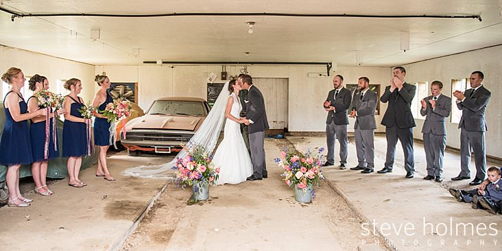 42_Bride and groom have first kiss in barn as bridal party looks on.jpg