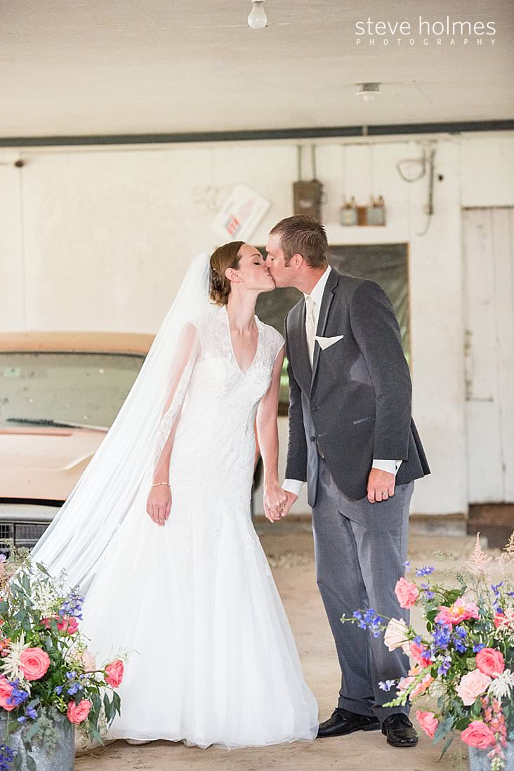 43_Bride and Groom kiss at alter in barn_.jpg