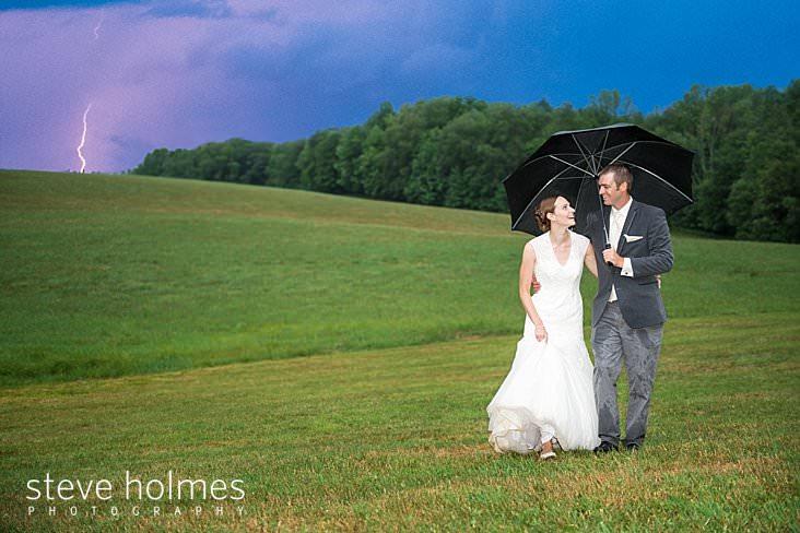 53_Bride walks with groom in field under umbrella as lightening strikes in background.jpg